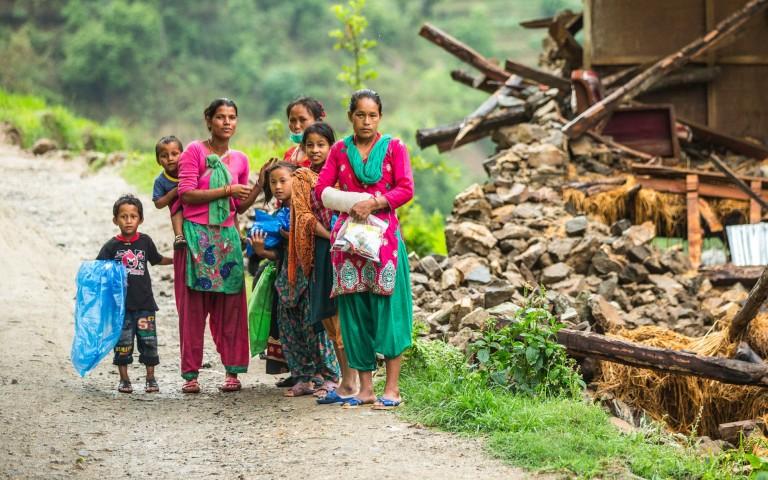 A family beside a damaged house near Naglebhare, Nepal