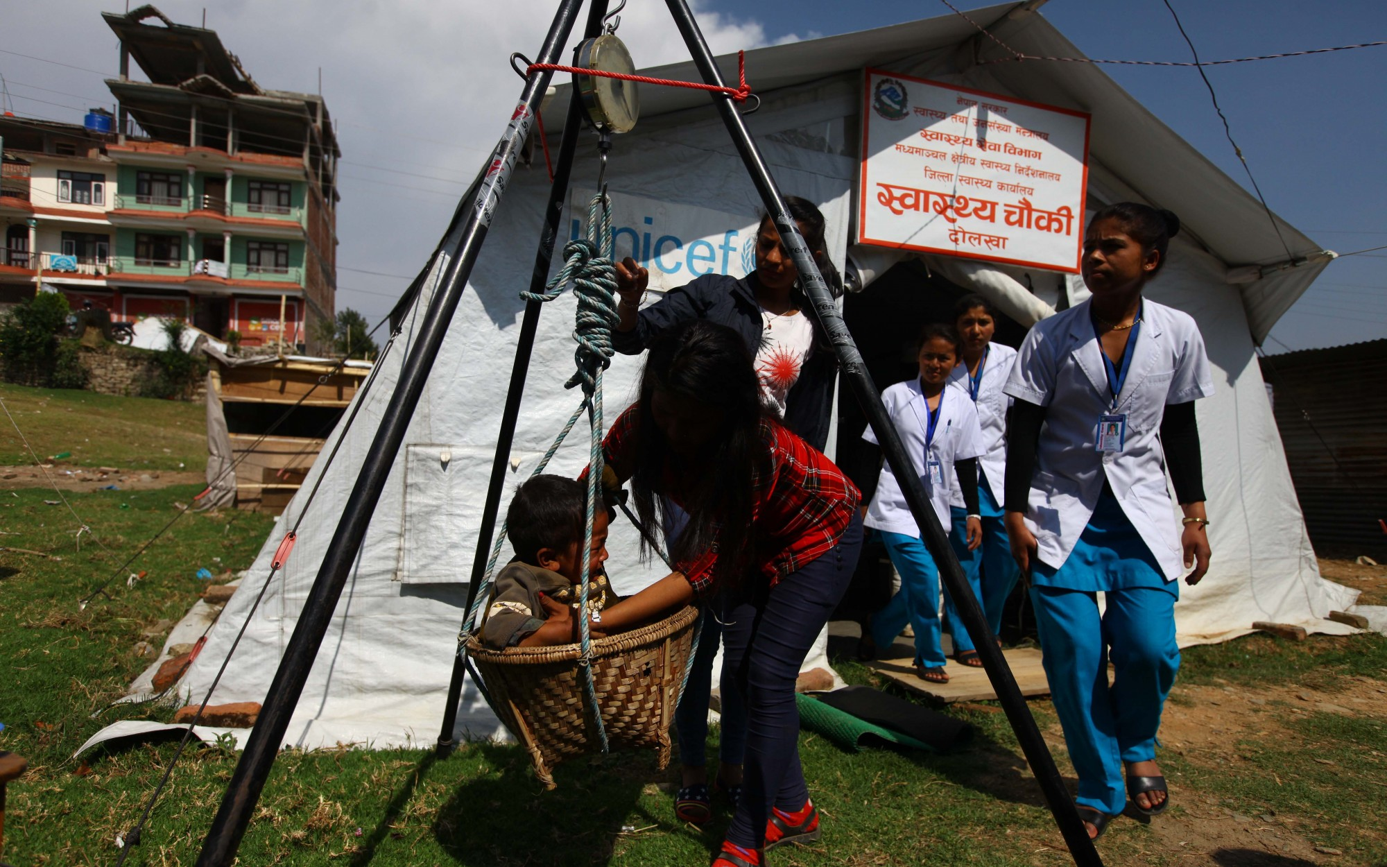 A baby being weighed outside a tent in a health post in Dolakha district