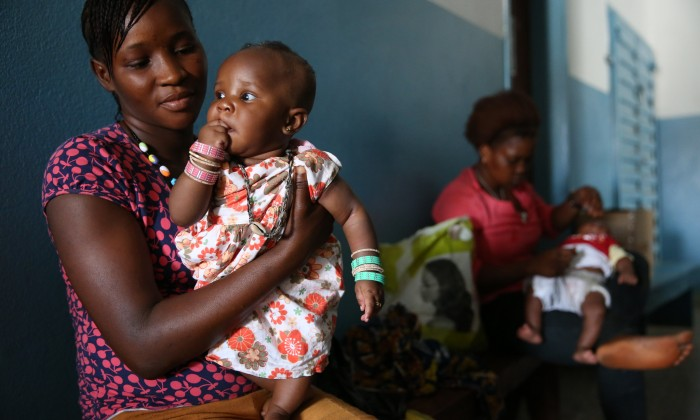 Mary Thullah 20-year old mom comforts her daughter Fatmata Turay after she received vaccinations at the Princess Christian Maternity Hospital on March 10, 2015 in Freetown Sierra Leone. (Dominic Chavez/World Bank, 2015)
