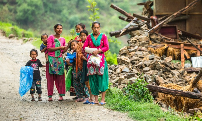 A family beside a damaged house near Naglebhare, Nepal